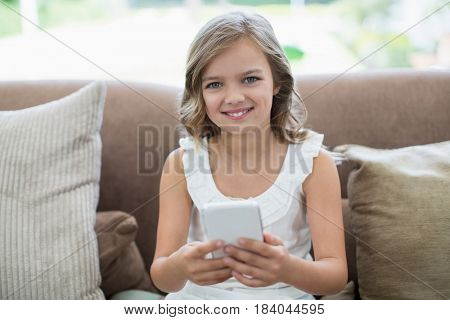 Portrait of smiling girl sitting on sofa using mobile phone in living room at home
