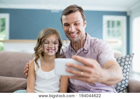 Smiling father and daughter sitting on sofa and taking selfie in living room at home