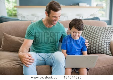 Smiling father and son sitting on sofa using laptop in living room at home