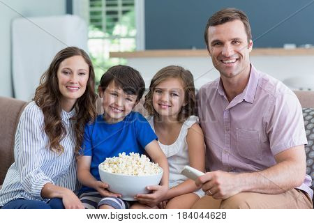 Portrait of smiling family watching tv and eating popcorn in living room at home