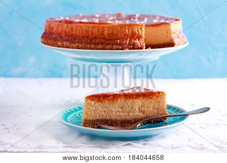 Salted caramel cheesecake sliced on blue plate