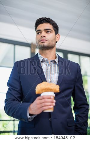 Businessman holding disposable coffee cup and croissant in a restaurant
