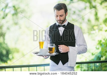 Male waiter holding tray with beer glass and coffee cup in restaurant