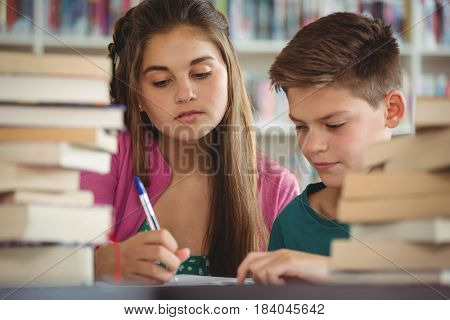 Attentive school kids doing homework in library at school