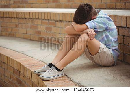 Sad schoolboy sitting alone on steps in campus at school