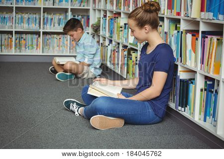 Attentive school kids reading books in library at school
