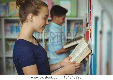 Smiling schoolgirl reading book in library at school