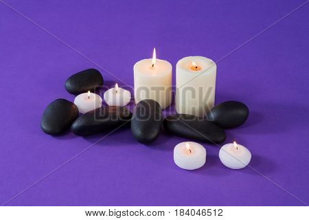 Lit candles and zen stones on purple background