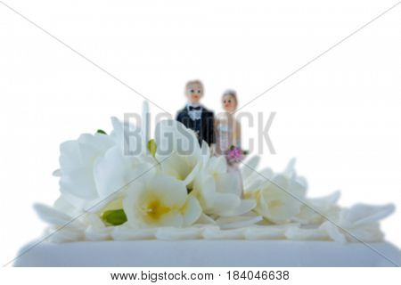 Wedding cake with couple figurines and flowers against white background