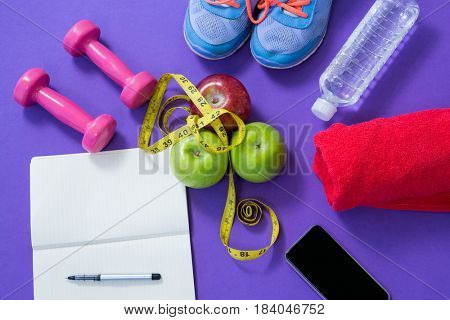 Fitness accessories with opened book, apples, mobile phone and measuring tape on purple background
