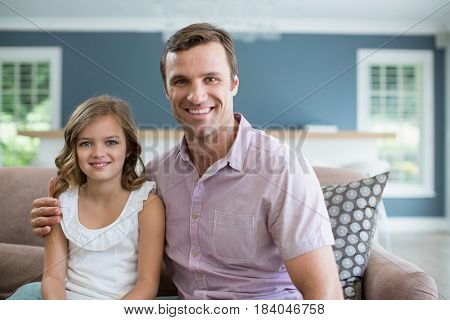 Portrait of smiling father and daughter sitting on sofa in living room at home