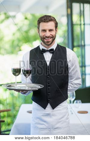 Portrait of male waiter male waiter holding tray with wine glasses in the restaurant