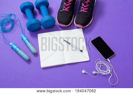 Fitness accessories with opened book and mobile phone on purple background