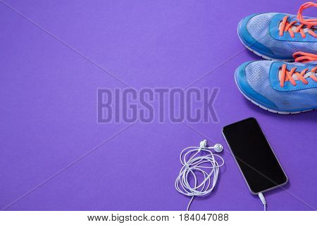 Sneakers, mobile phone with headphones on purple background