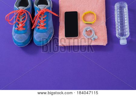 Sneakers, water bottle, towel, mobile phone with headphones and fitness band on purple background