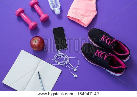 Fitness accessories with opened book, apple, mobile phone, headphones on purple background