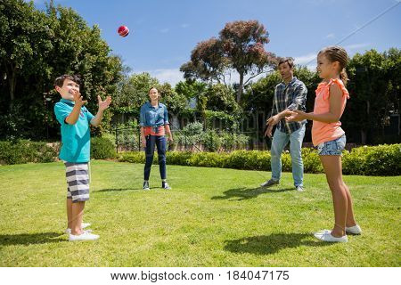 Happy family playing with the ball in park on a sunny day