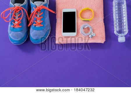 Sneakers, water bottle, towel, mobile phone with headphones and wristband on purple background