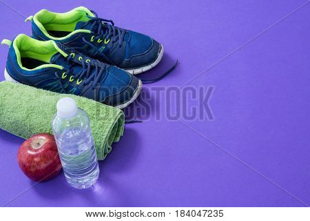Water bottle, towel, apple and sneakers on purple background
