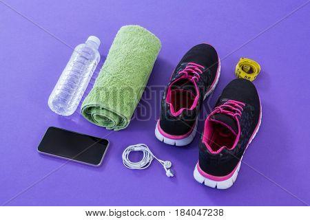 Sneakers, water bottle, towel, measuring tape, mobile phone and headphones on purple background