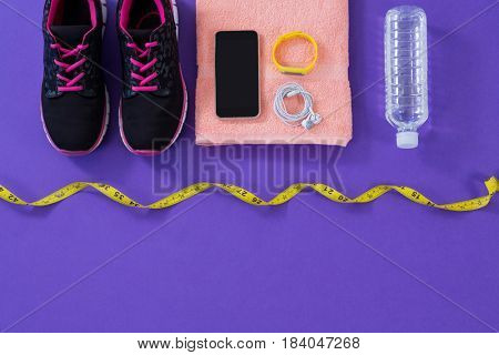 Sneakers, water bottle, towel, measuring tape mobile phone with headphones and fitness band on purple background