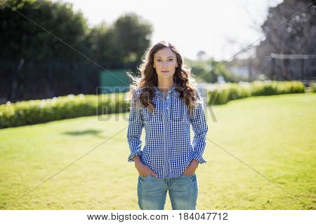 Portrait of woman standing with hands in pocket at park