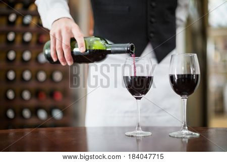 Mid-section of male waiter pouring wine in wine glasses