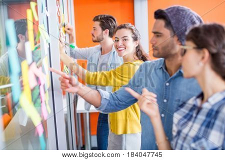Executives reading sticky notes on glass wall in office