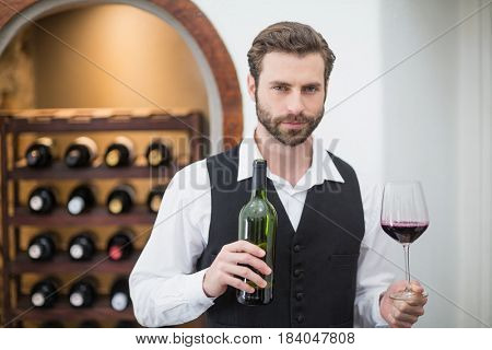 Portrait of male waiter holding wine glass and wine bottle in the restaurant