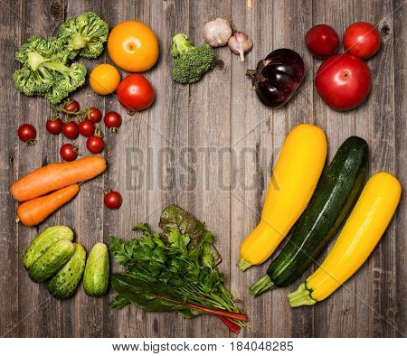 Fresh ingredients for cooking on rustic weathered wood background top view place for text. Vegetables frame. Vegan food vegetarian and healthily eating concept.