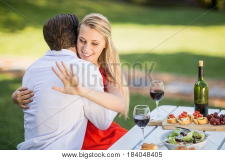 Beautiful woman looking at her ring while hugging the man