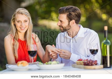 Man putting a ring on womans finger in the restaurant