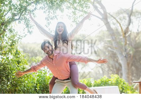 Portrait of man giving piggyback ride to woman in the restaurant