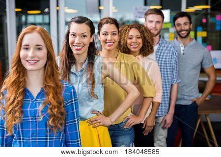 Portrait of smiling executives standing in a row at office