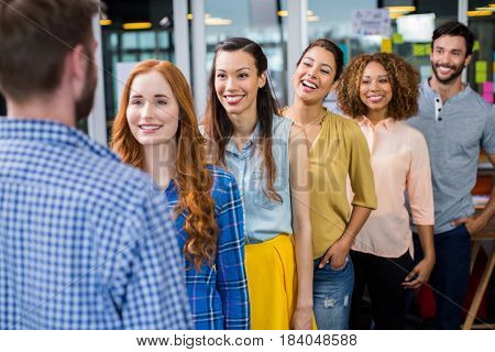 Smiling colleagues standing in front of male executive at office