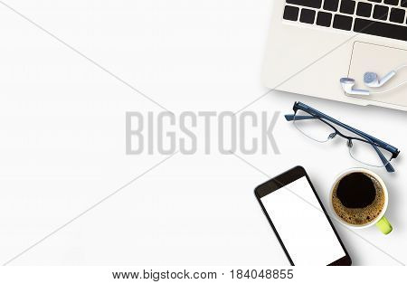 White office desk with laptop eye glasses earphone and cup of coffee.Top view with copy space flat lay. Office desk table concept.