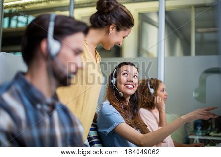 Female customer service executive interacting with her colleague at desk in office