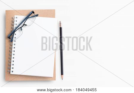 Blank notebook with pencil and eyeglasses on white background suit for writing and thinking concept. Top view with copy space (selective focus). Office desk table concept.