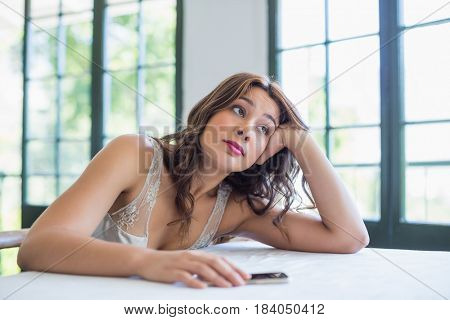 Beautiful woman with mobile phone resting on her elbow in the restaurant