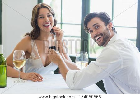 Portrait of man proposing a woman with a ring in the restaurant