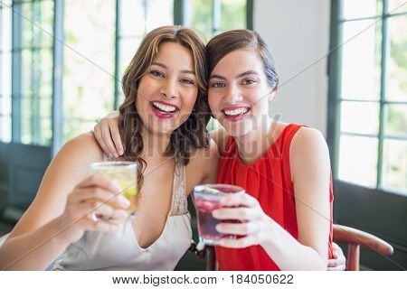 Portrait of happy friends hugging each other while holding cocktail glasses
