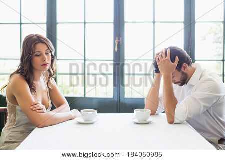 Depressed couple sitting with coffee cup in the restaurant