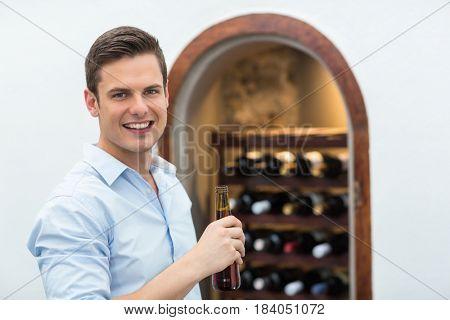 Portrait of handsome man holding beer bottle