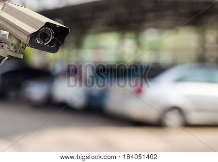 Image of CCTV security camera on blur car parking background