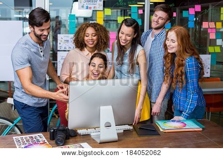 Smiling graphic designers interacting with each other while working at desk in office