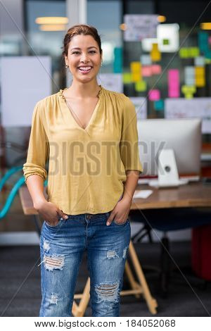 Portrait of smiling female executive standing with hands in pocket at office