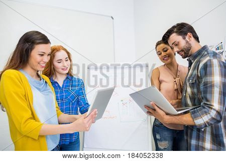 Smiling executives discussing over digital tablet and laptop in conference room meeting at office