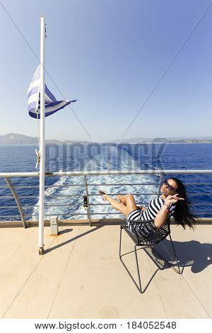 Girl in dress on the ship near large Greek flag the landscape of the city of Zakynthos in the background
