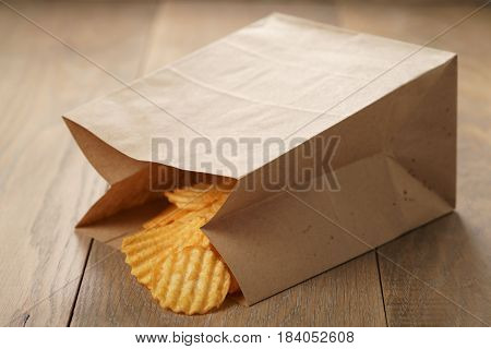 rippled potato chips with paprika in paper bag, shallow focus