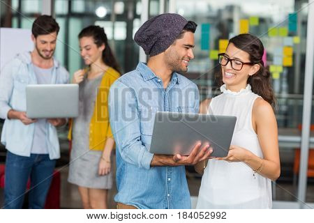 Smiling executives using laptop in office